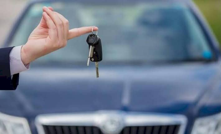 hand holds keys in front of new car purchased with a car loan