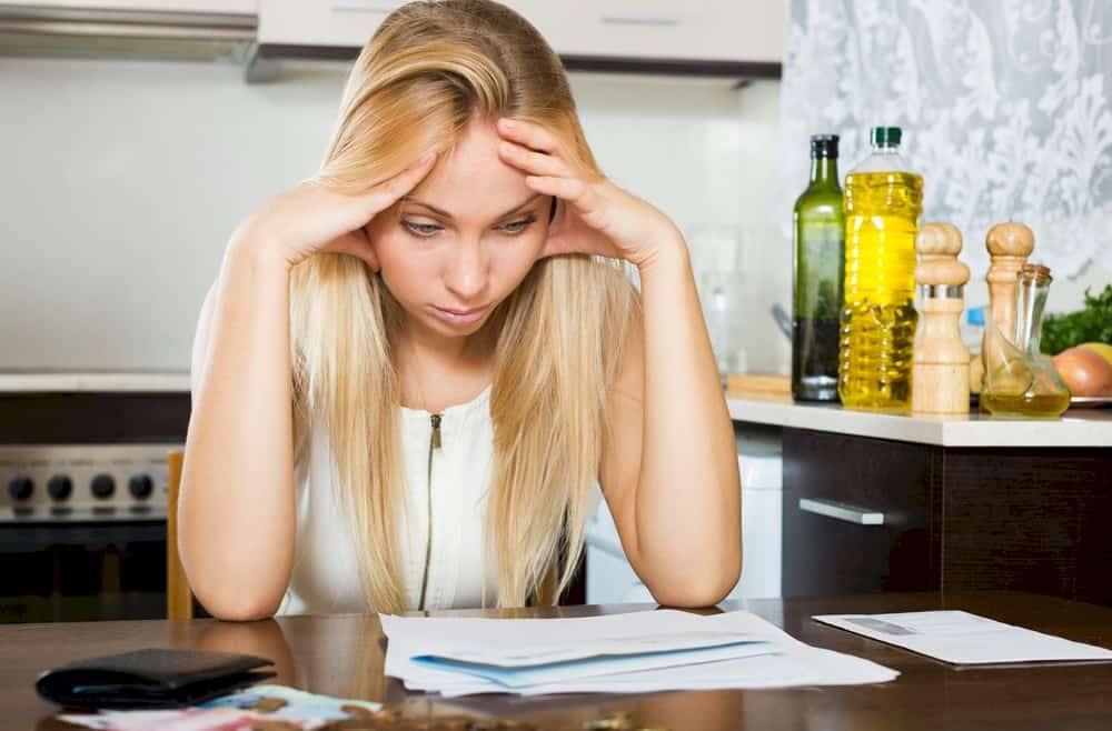 Woman at table, stressed enough to consider debt consolidation loans
